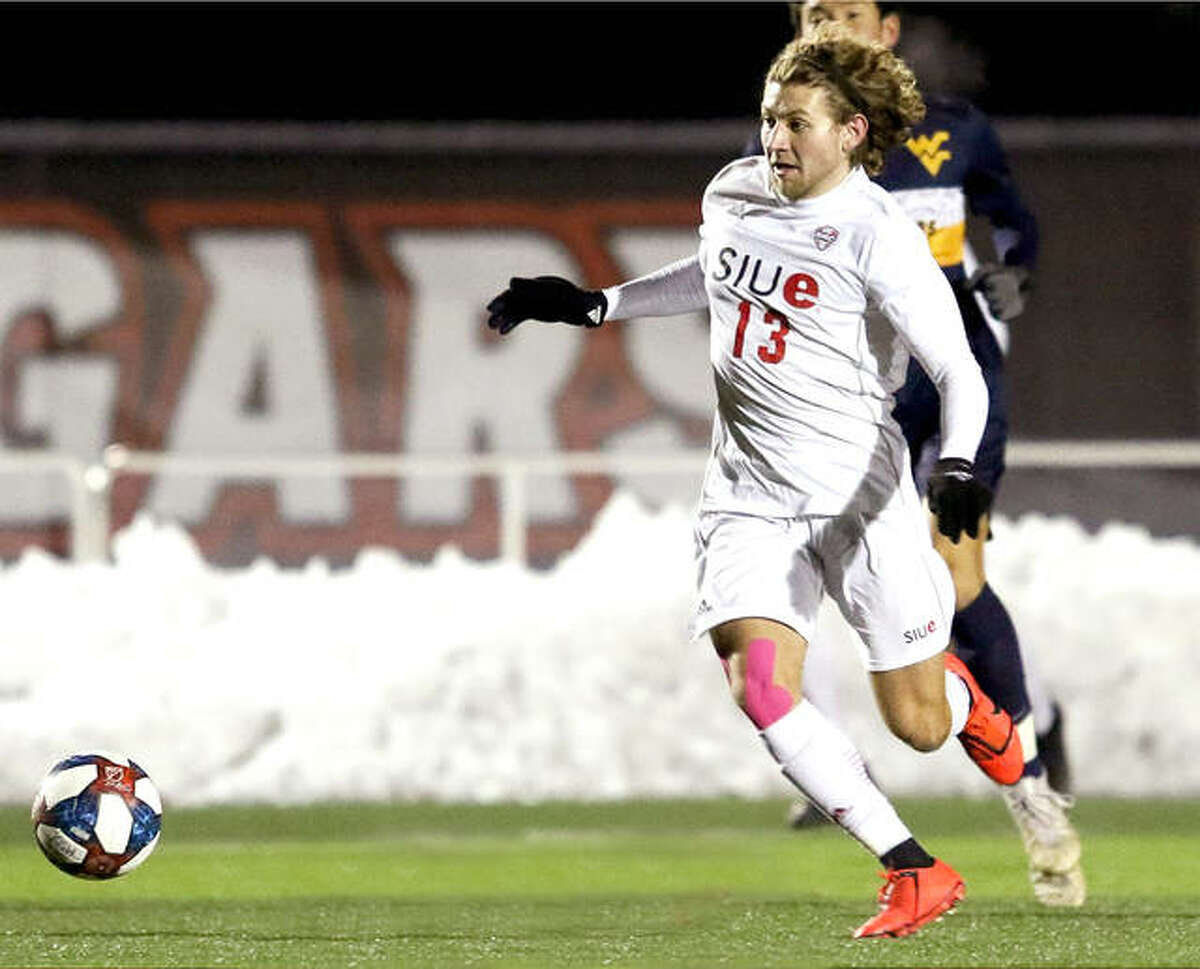 Kelby Phillips of SIUE (13) battles a West Virginia player for possession of the ball during a Mid-American Conference Tournament quarterfinal game Nov. 12, 2019 at Korte Stadium. It was the last time SIUE's men's soccer team played a game. The 2020 fall season was postponed to next February because of the virus pandemic.