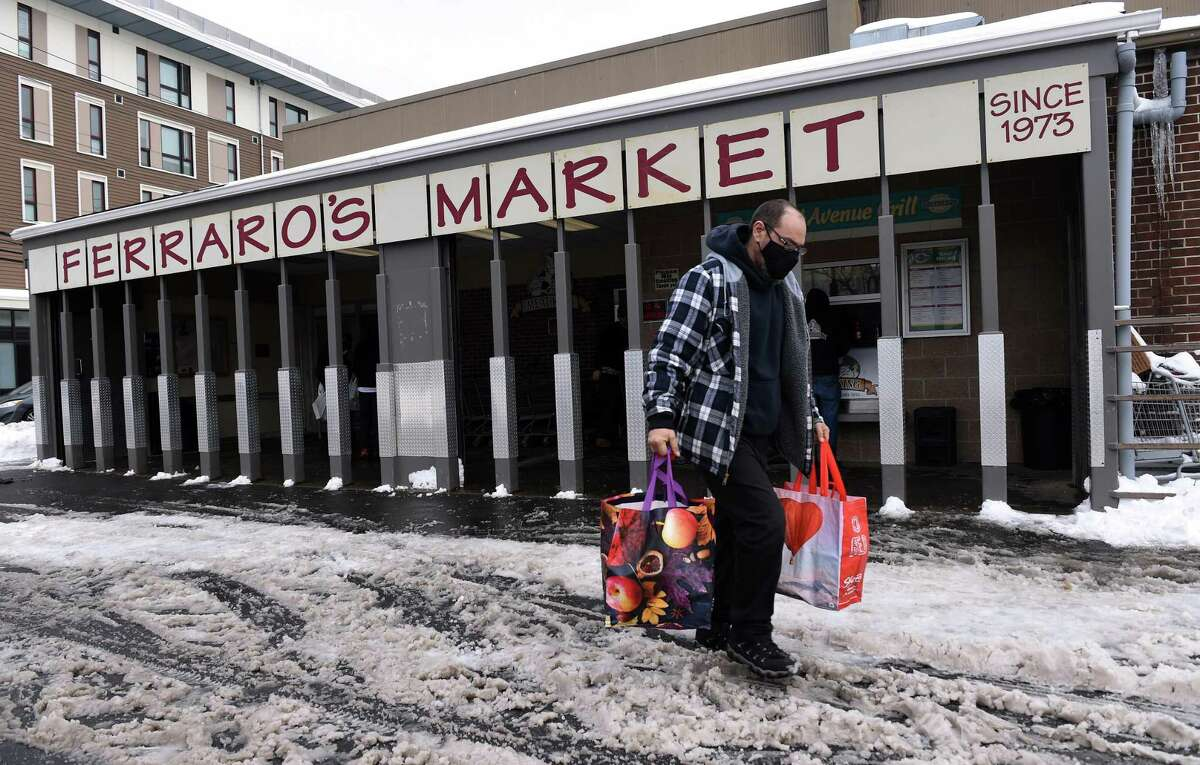 Joe DiVincenzo of New Haven carries his groceries to his car at Ferraro's Market in New Haven on December 18, 2020.