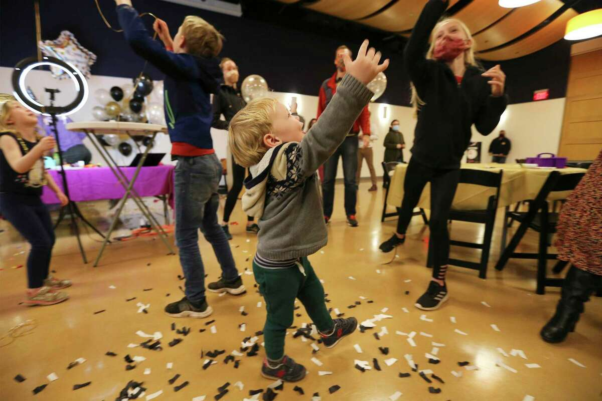 """The MacNamara family, including 3-year-old August, help ring in the """"nnon"""" year at the DoSeum's daytime New Year's Eve celebration Thursday, Dec. 31, 2020. Program organizers invited families who were visiting the museum to participate in the virtual countdown."""