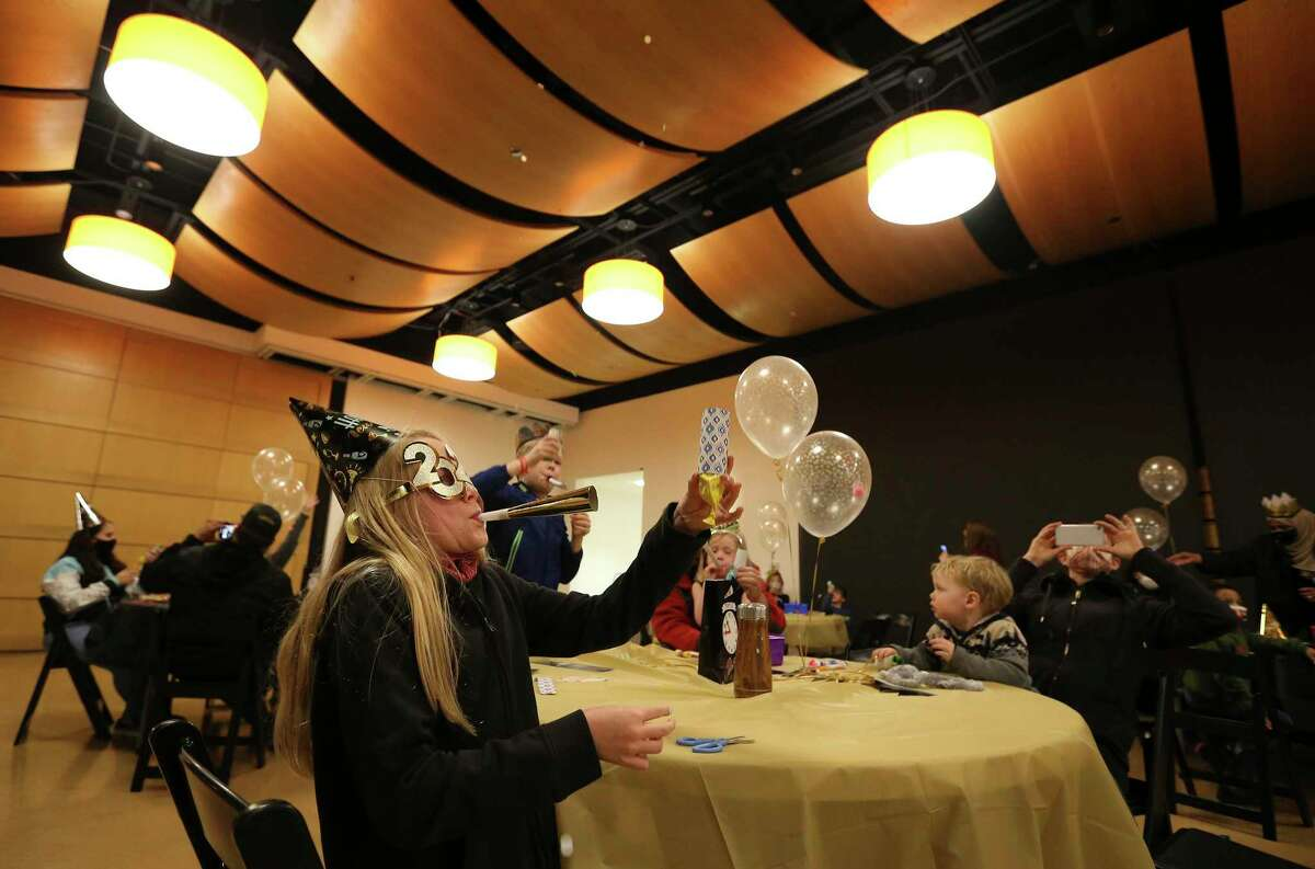 Molly MacNamara, 10, of College Station blows a horn and sends confetti into the air as the DoSeum celebrates the new year. Families made confetti poppers and then launched them at noon on New Year's Eve.