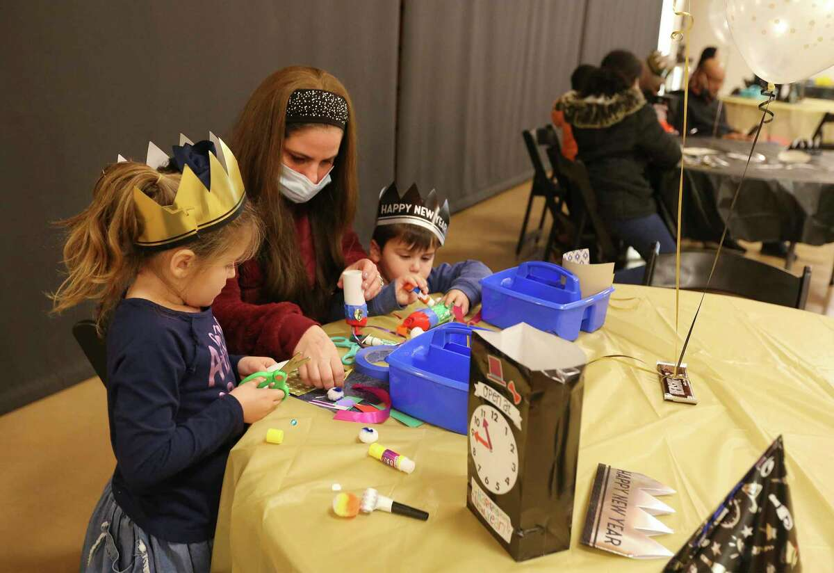 Menucha Berkson helps her children, Hadassah, 6, and Avraham, 4, to make party poppers at the DoSeum's New Year's Eve celebration.