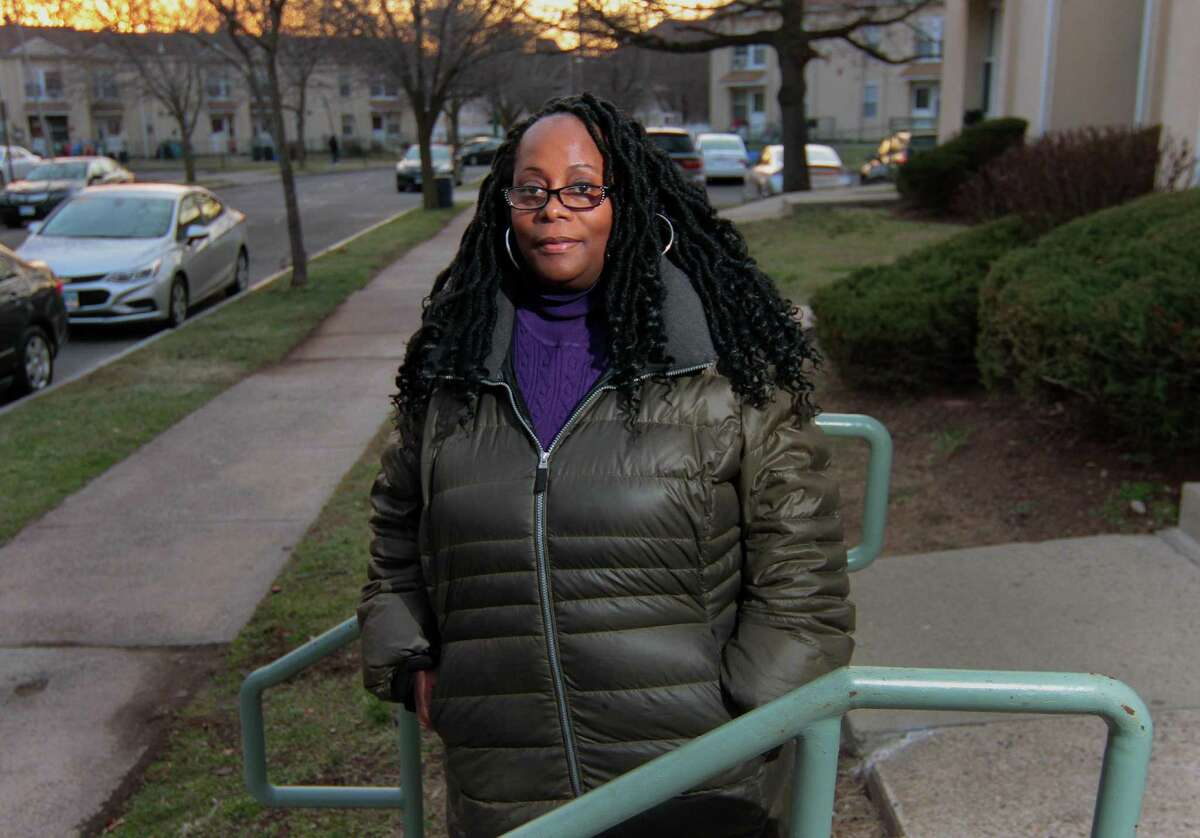Sylvia Cooper poses outside of her apartment in New Haven Dec. 30, 2020. Cooper works on a state contract interviewing people in need during the pandemic to help connect them with resources. But after losing income because in-person work couldn't happen anymore, she is welcoming the stimulus money to help her make ends meet.