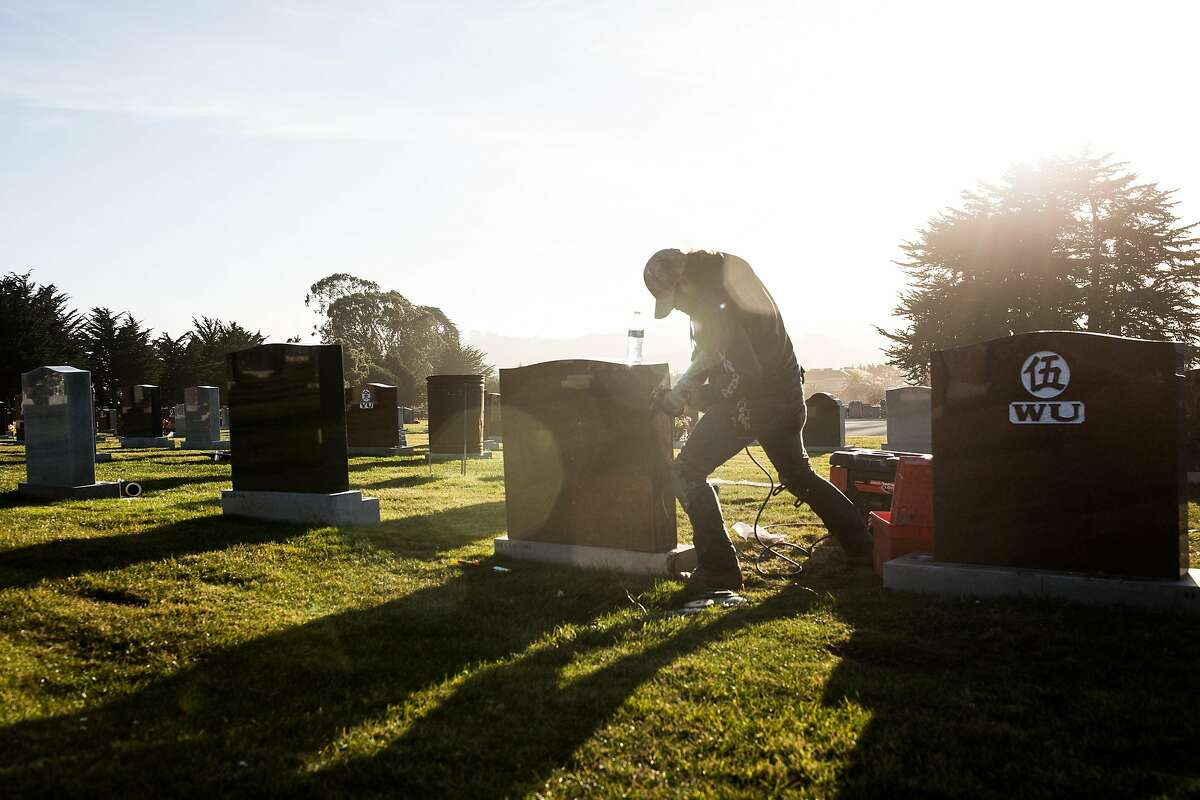 Jose Dardano repairs a headstone at Cypress Lawn Cemetery on Thursday, December 31, 2020