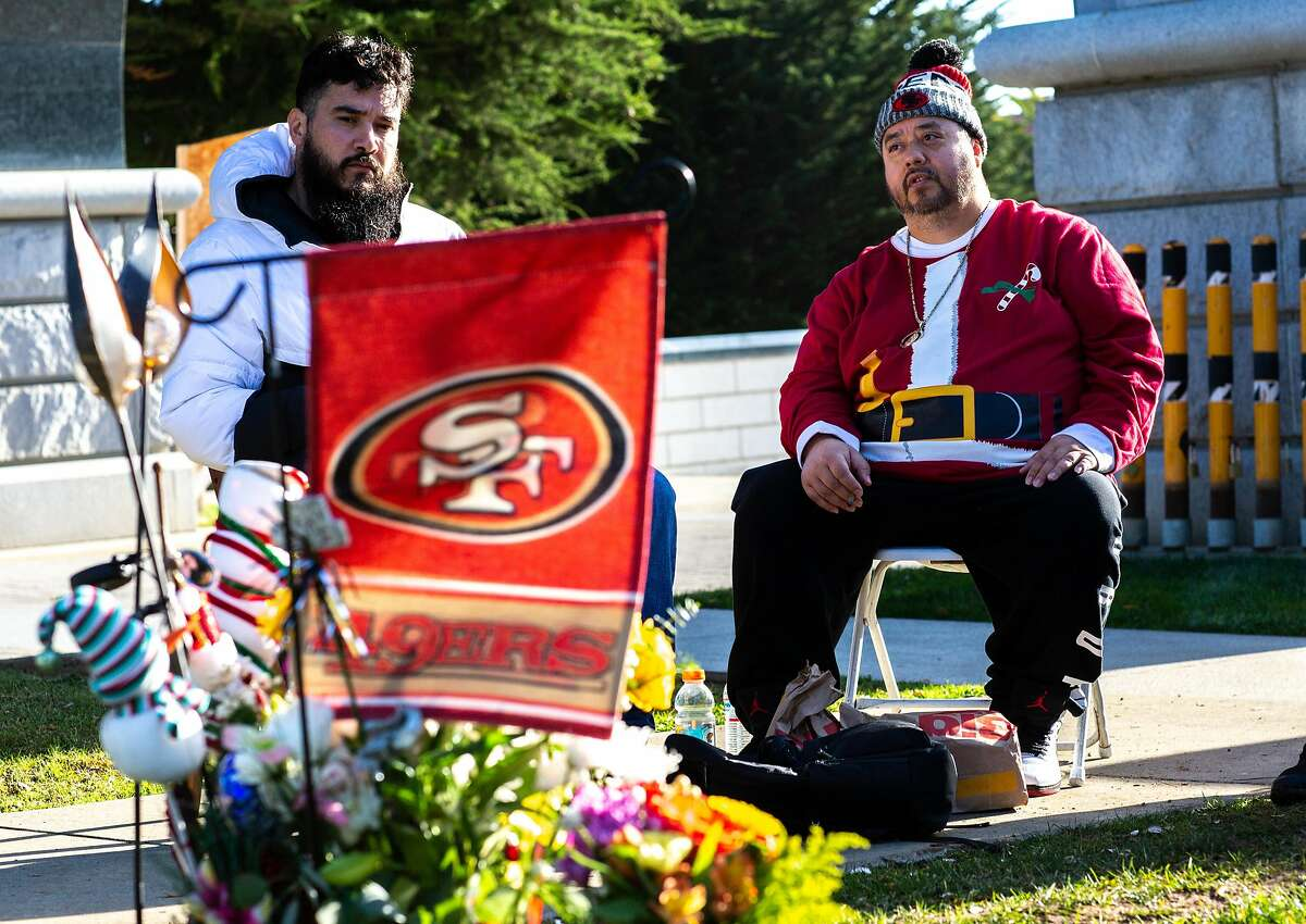 Omar Lemus (R) visits his brothers grave who passed this year with close family friend George Escobar at Cypress Lawn Cemetery on Thursday, December 31, 2020. Lemus is wearing the gag shirt that his brother had gotten him.