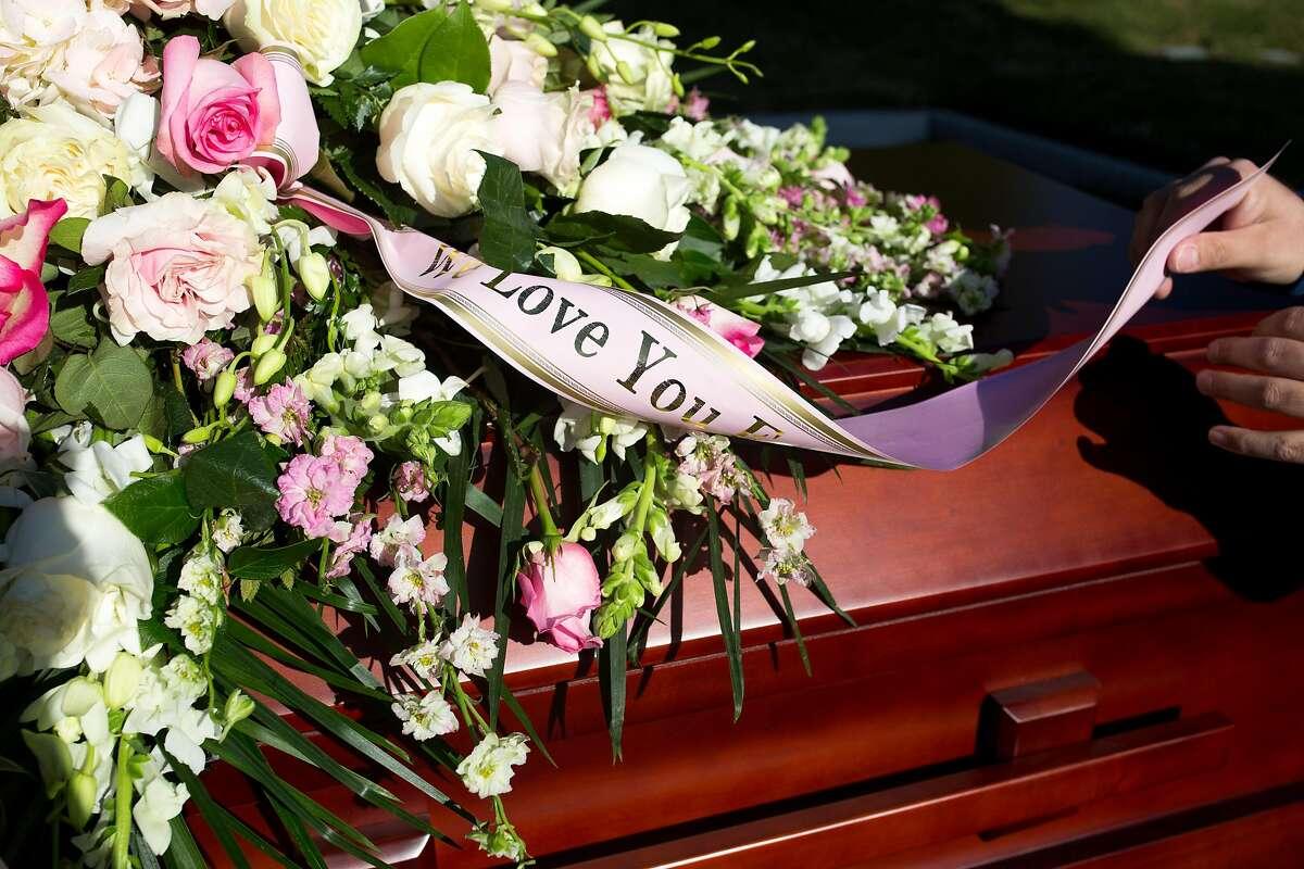 A flowers arrangement is seen on a casket at Cypress Lawn Cemetery on Thursday, December 31, 2020