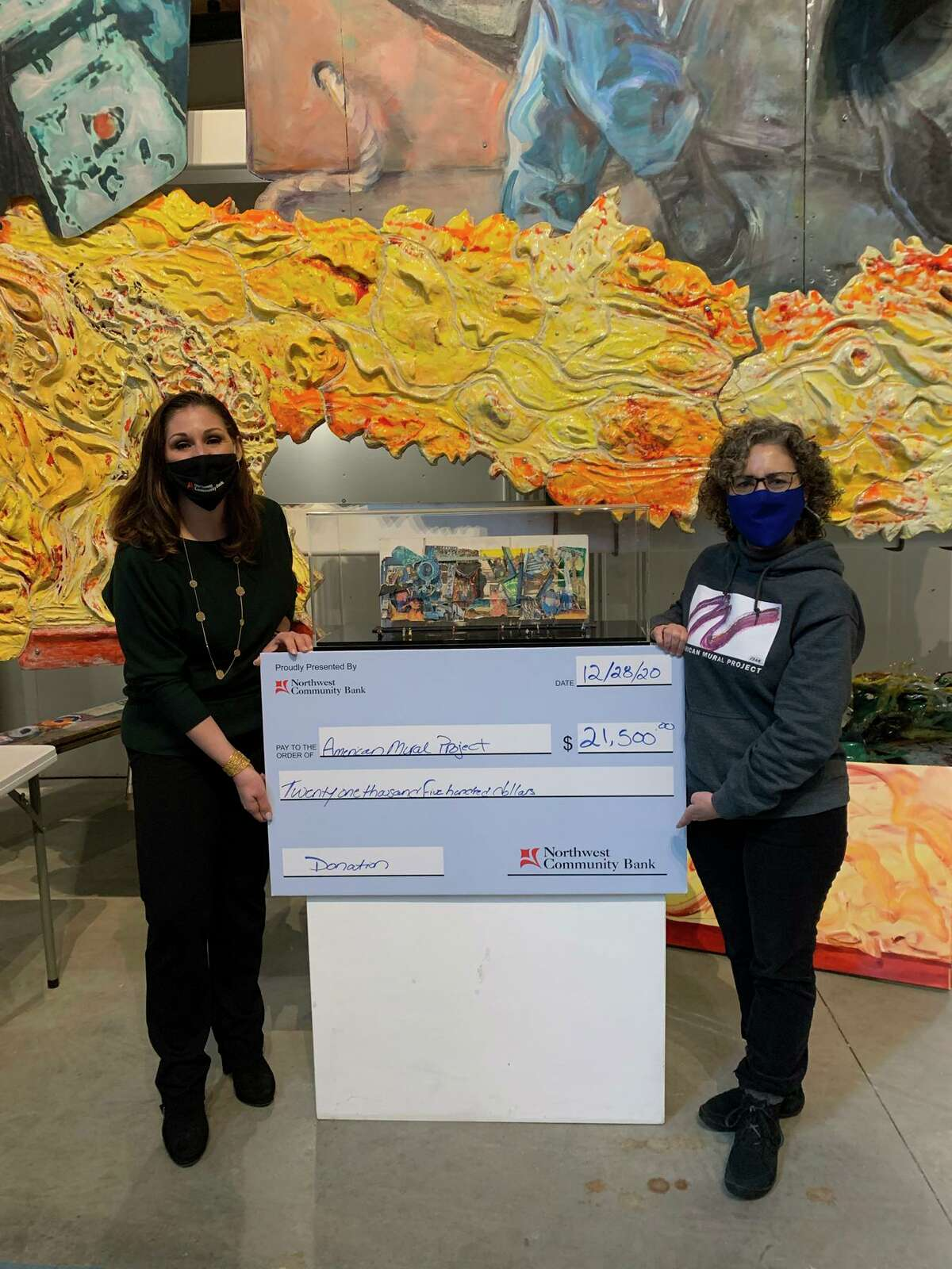 Dea Pitruzzello, Northwest Community Bank Vice President, Branch Administration, presents a $21,500 donation to American Mural Project to Executive Director Amy Winn.
