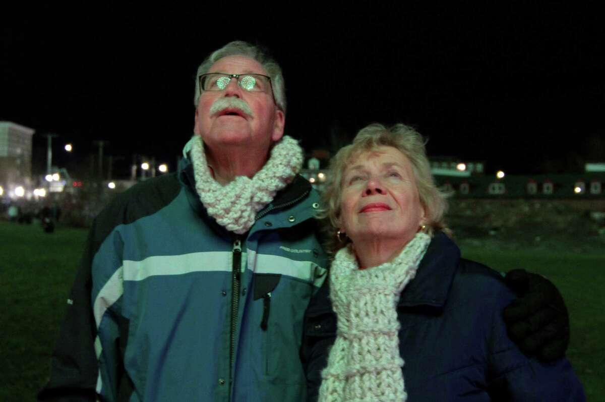 A couple enjoys fireworks which were held to help ring in the new year at Veterans' Riverwalk Park in Shelton, Conn., on Thursday Dec. 31, 2020.