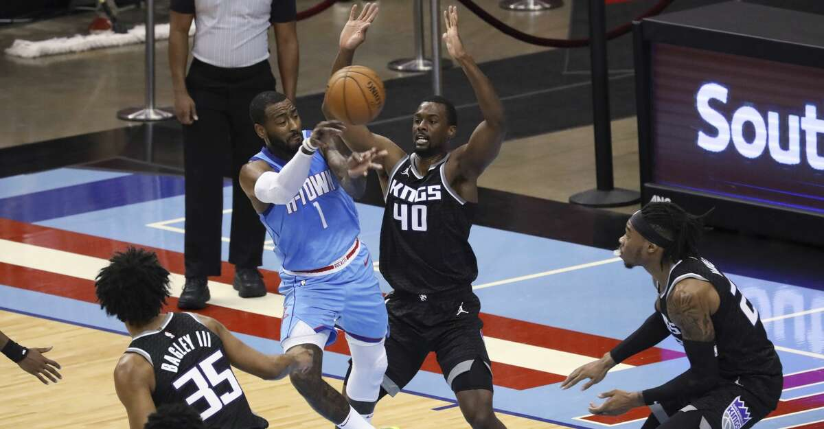 Houston Rockets guard John Wall passes the ball around Sacramento Kings' Harrison Barnes during the first half of an NBA basketball game Thursday, Dec. 31, 2020, in Houston. (AP Photo/Richard Carson)