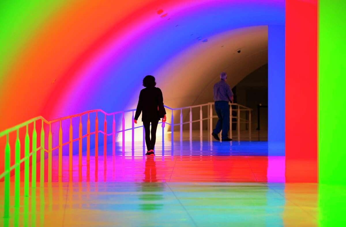 """People move through Carlos Cruz-Diez's """"Cromosaturación MFAH,"""" a new tunnel connecting The Museum of Fine Arts Houston's new Nancy and Rich Kinder Building to the rest of the campus, Wednesday, Nov. 18, 2020, in Houston."""