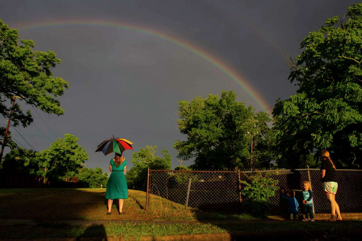 Neighbors Laura Livingston (with umbrella) and Eva Preisner with her two children, Hans, 5, and Eda Elaine, 2, look at a rainbow crossing a drainage ditch in their Westbury neighborhood, Friday evening, May 15, 2020, in Houston.
