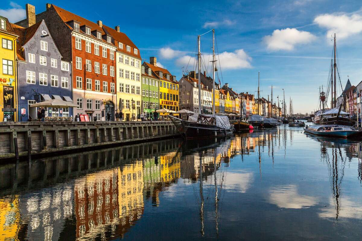 Nyhavn is a 17th-century waterfront, canal and entertainment district in Copenhagen, Denmark. Stretching from Kongens Nytorv to the harbour front just south of the Royal Playhouse, it is lined by brightly colored 17th and early 18th century townhouses and bars, cafes and restaurants. Serving as a