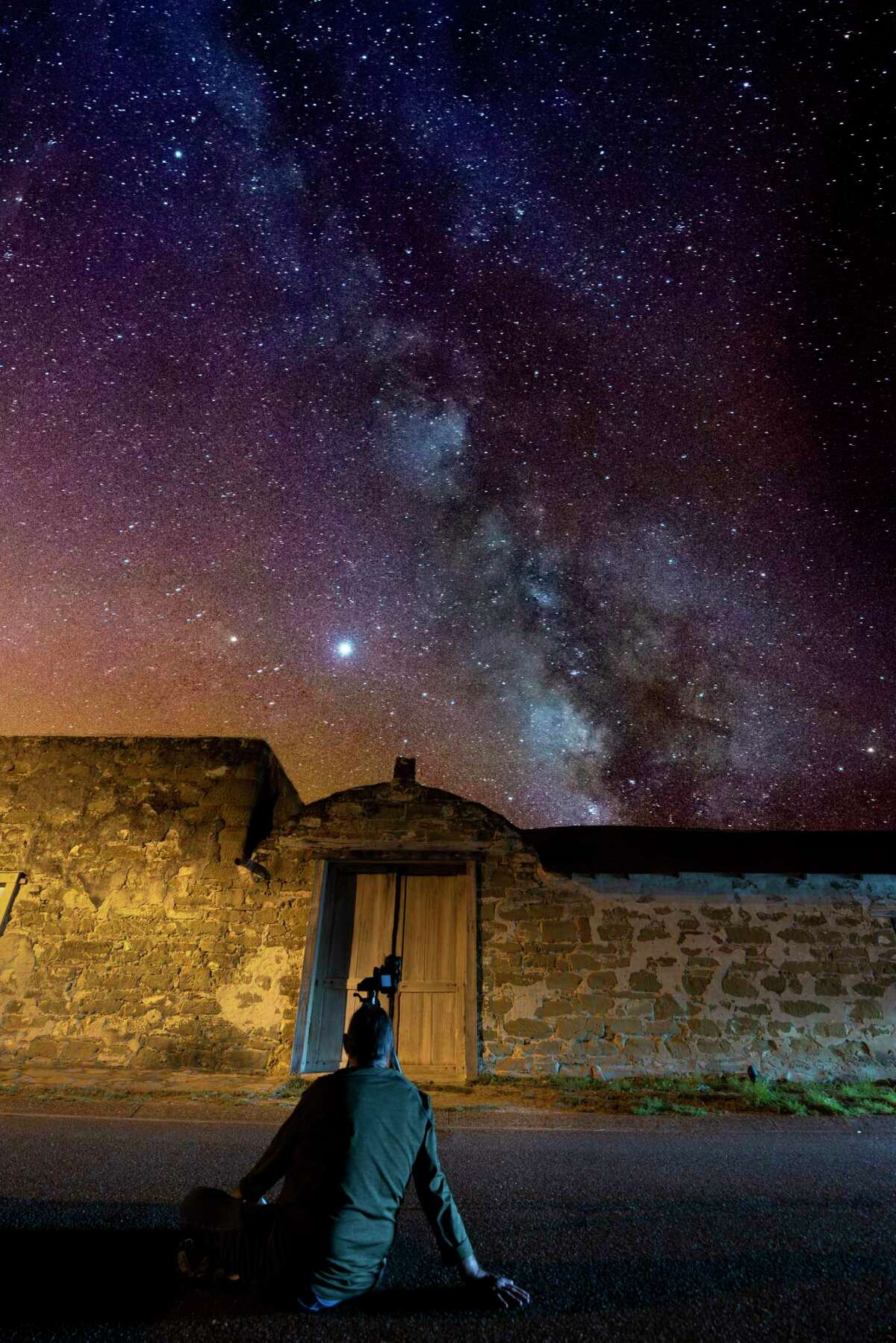 A photo illustration pictures longtime LMT photographer Cuate Santos viewing the night sky, with the visible milky way actually a previous image Santos took in San Ygnacio.