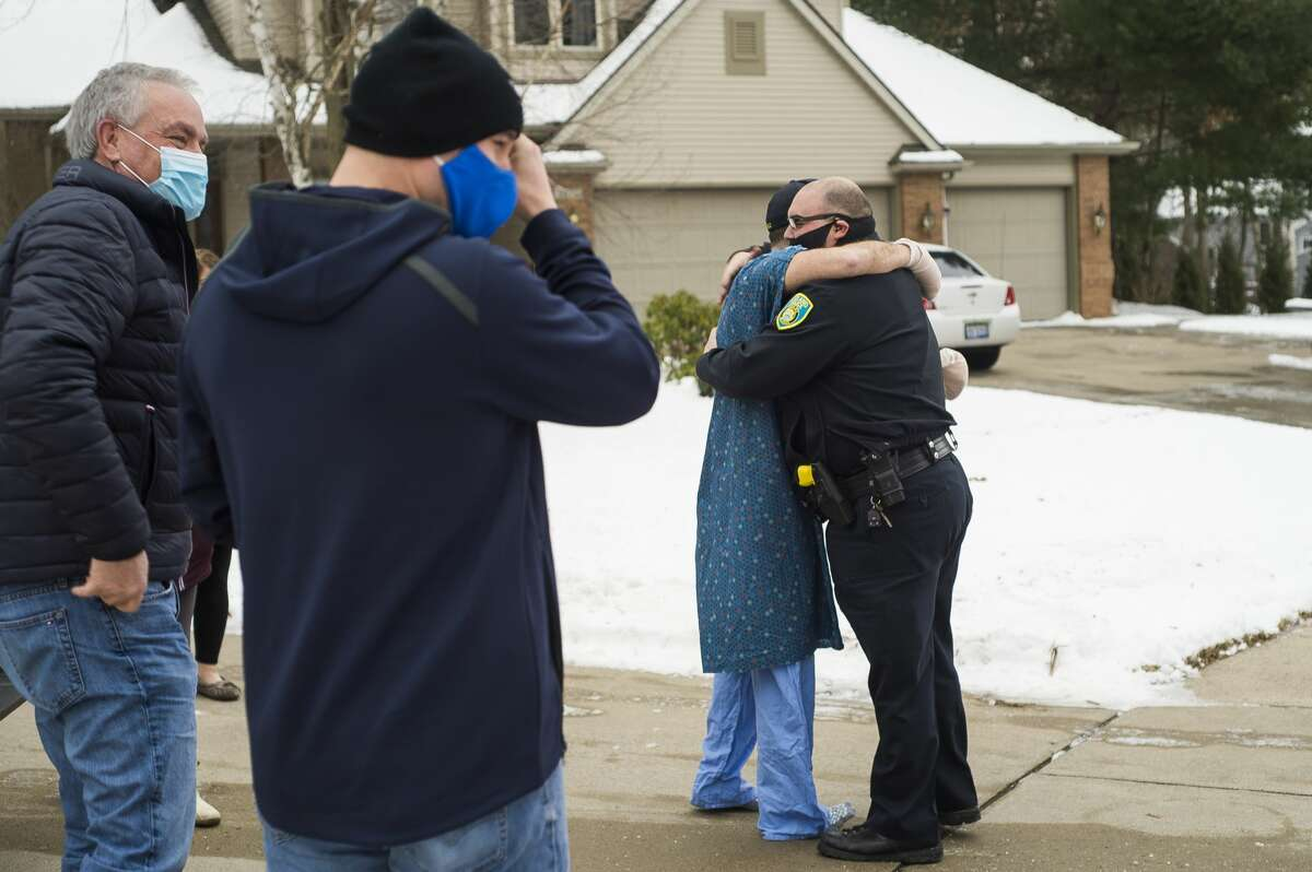 Midland Police Officer Tyler Hollingsworth greets his fellow officers after they escorted him back home Friday, Jan. 1, 2021 from his stay at Hurley Medical Center in Flint after he sustained injuries in the line of duty on Christmas Eve. (Katy Kildee/kkildee@mdn.net)