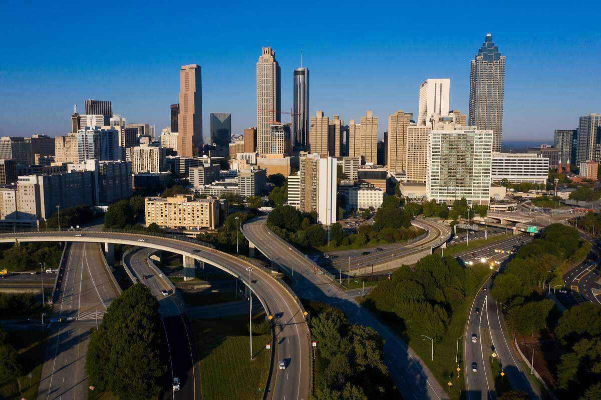 Vehicles travel along a highway in downtown Atlanta, Georgia, U.S., on Friday, Oct. 2, 2020. Bloomberg News analyzed foot traffic data for downtown merchants in Lower Manhattan, Chicago, Atlanta, Dallas and San Francisco and compared them to merchants in five nearby suburbs for the period spanning mid-October through November -- a period that included Black Friday. The downtown merchants saw an average foot traffic decline of between 64% and 77% for the period. Photographer: Dustin Chambers/Bloomberg