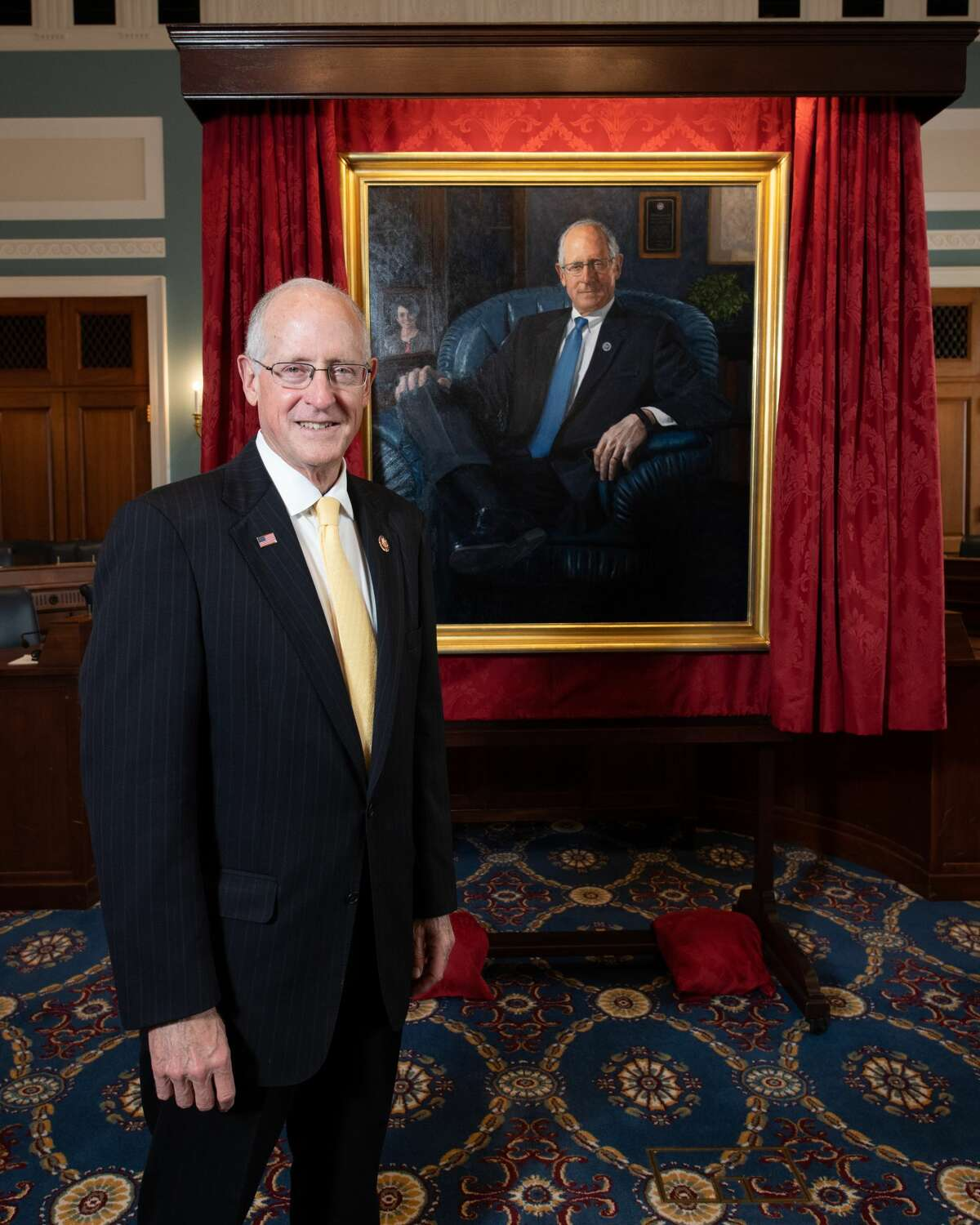 U.S. Rep. Mike Conaway stands in front of a portrait of him.