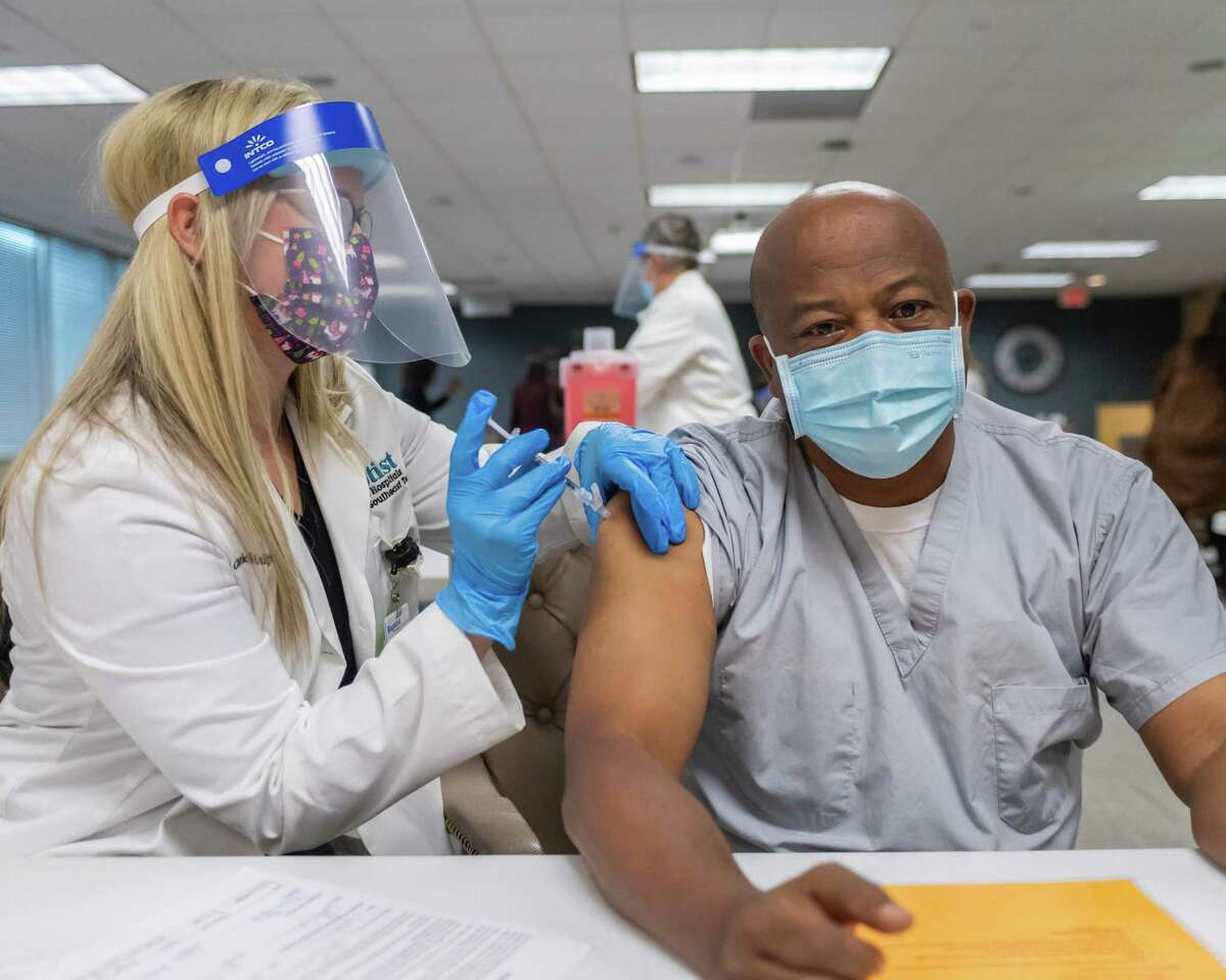 Clinical pharmacy specialist Corrie Malphrus, PharmD injects Emergency Room Director Dr. Ali Osman, MD with the coronavirus vaccine. Baptist Hospital administered the first of their Covid-19 vaccines to 5 doctors on the pandemic frontlines Friday morning. Photo made on December 18, 2020. Fran Ruchalski/The Enterprise