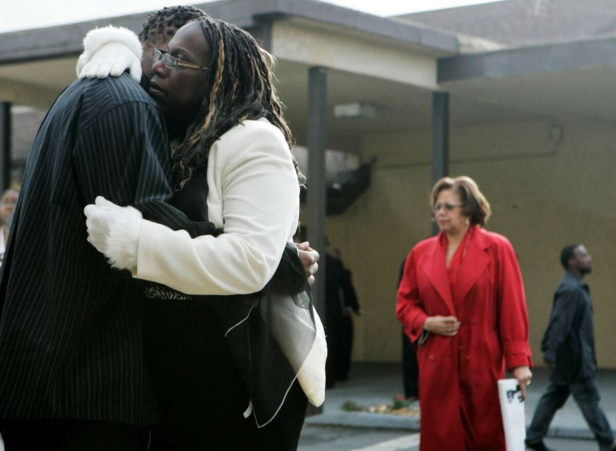 Mourners embrace during the funeral of Oscar Grant at the Palma Ceia Baptist Church in Hayward, Calif., Wednesday, Jan. 7, 2009. Grant was shot and killed by a police officer after an altercation on a BART train station platform in Oakland, Calif. on New Year's Day.