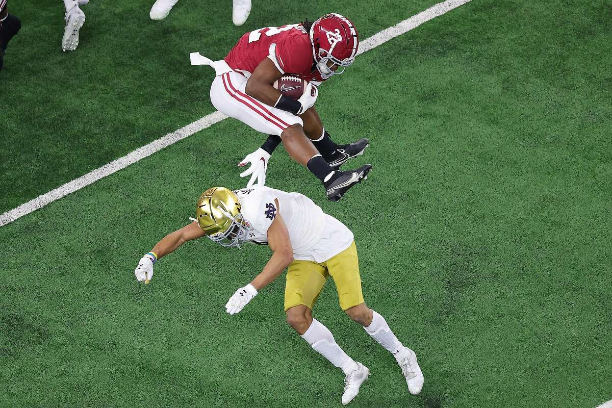 Running back Najee Harris #22 of the Alabama Crimson Tide leaps cornerback Nick McCloud #4 of the Notre Dame Fighting Irish during the first quarter of the 2021 College Football Playoff Semifinal Game at the Rose Bowl Game presented by Capital One at AT&T Stadium on January 01, 2021 in Arlington, Texas.