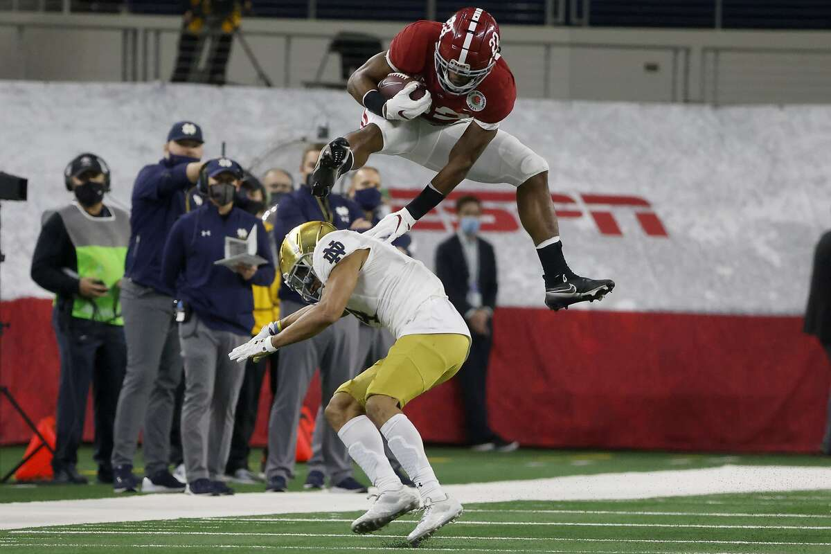 Alabama running back Najee Harris (22) hurdles Notre Dame cornerback Nick McCloud (4) as he carries the ball for a long gain in the first half of the Rose Bowl NCAA college football game in Arlington, Texas, Friday, Jan. 1, 2021.