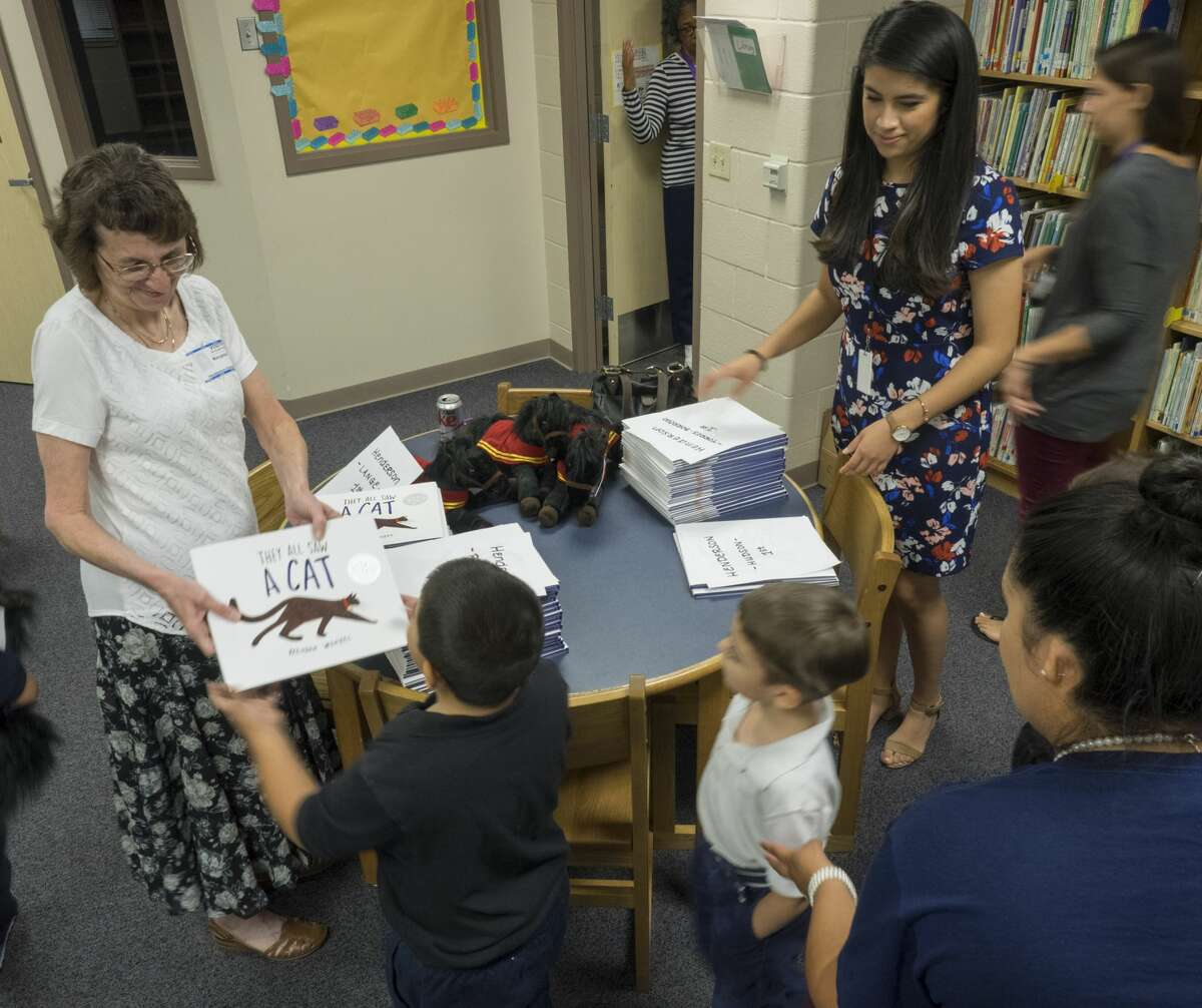"""Former Reporter-Telegram Managing Editor Mary Dearen and current Online Editor Mercedes Cordero hand out """"They All Saw A Cat"""" to Henderson Elementary first-graders as part of Project Literacy in 2017. Tim Fischer/Reporter-Telegram"""