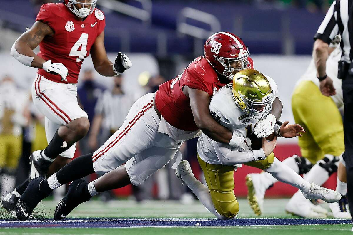 Quarterback Ian Book #12 of the Notre Dame Fighting Irish is sacked by defensive lineman Christian Barmore #58 of the Alabama Crimson Tide during the third quarter of the 2021 College Football Playoff Semifinal Game at the Rose Bowl Game presented by Capital One at AT&T Stadium on January 01, 2021 in Arlington, Texas.