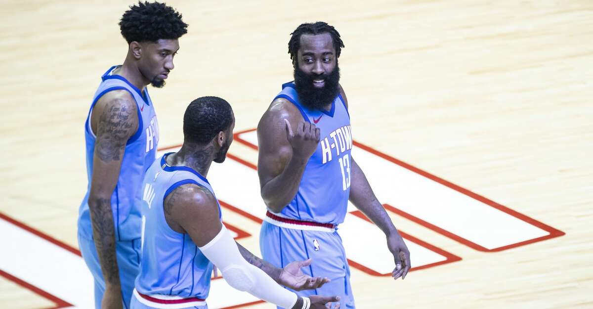 Houston Rockets guard James Harden (13), forward Christian Wood (35) and guard John Wall (1) walk to their bench for a timeout during the fourth quarter of the Houston Rockets 122-119 win over the Sacramento Kings on Thursday, Dec. 31, 2020, at Toyota Center in Houston.