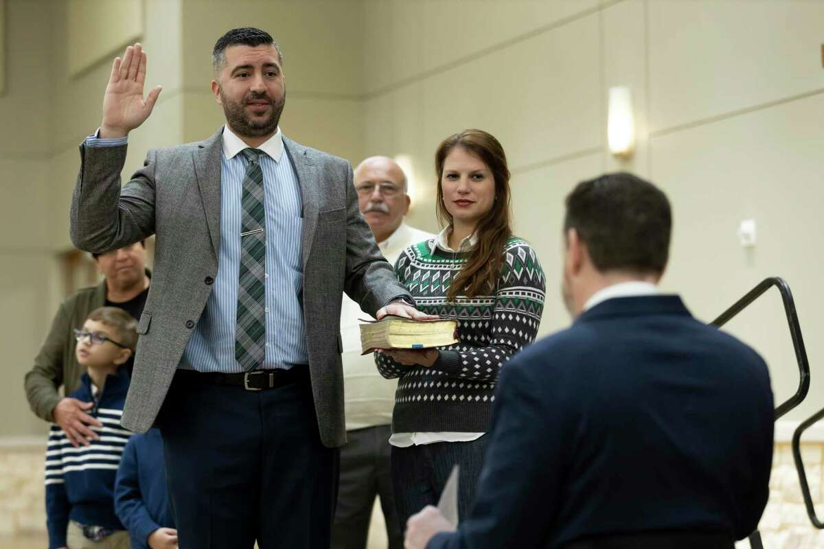 Vince Santini, 457th state District Court judge, raises his right hand while placing his left on a bible along side his wife Mary, as he's sworn in by 9th state District Court judge Phil Grant during a ceremony at the Lone Star Convention & Expo Center, Friday, Jan. 1, 2021, in Conroe.