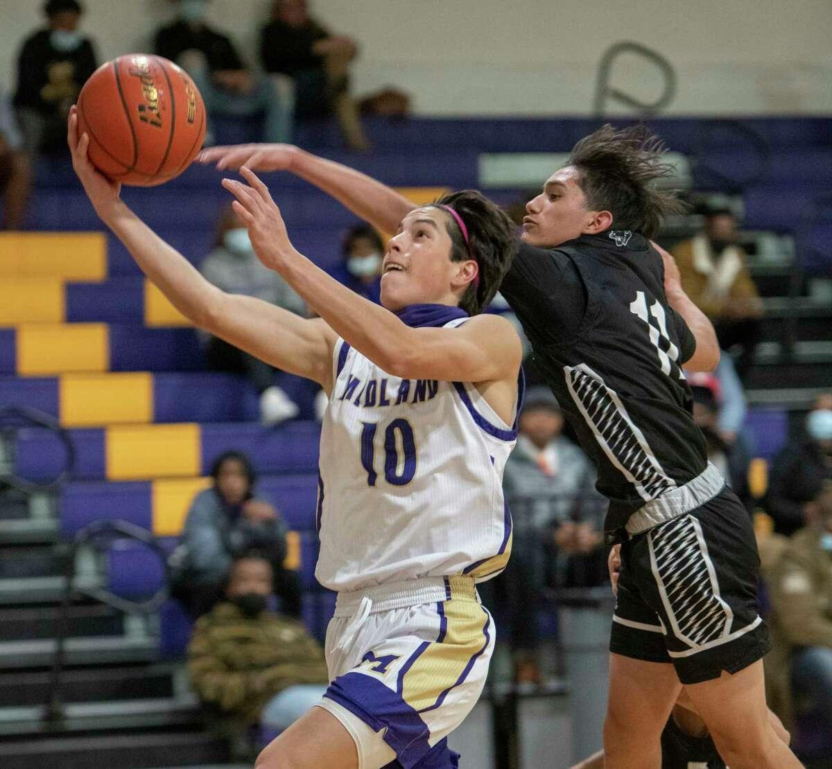 Midland High's Santiago Salcedo drives to the basket as Permian's Ben Salvidar tries to block him 01/01/2021 at Midland High gym. Tim Fischer/Reporter-Telegram