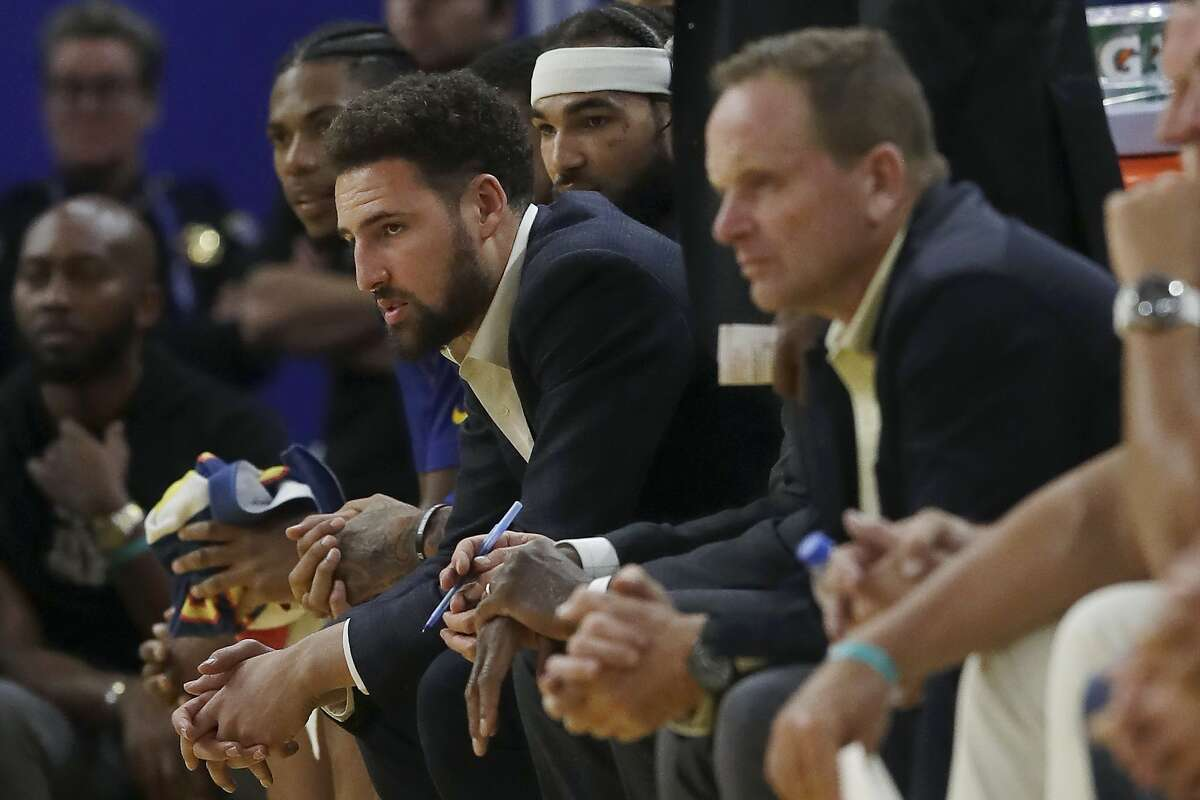 FILE - In this Nov. 4, 2019, file photo, injured Golden State Warriors guard Klay Thompson, center left, watches from the bench during the second half of an NBA basketball game against the Portland Trail Blazers in San Francisco. While Golden State is still dealing with the devastating news Splash Brother Klay Thompson will miss another season because of a torn right Achilles tendon that required surgery, everybody is eager for a fresh start.(AP Photo/Jeff Chiu, File)