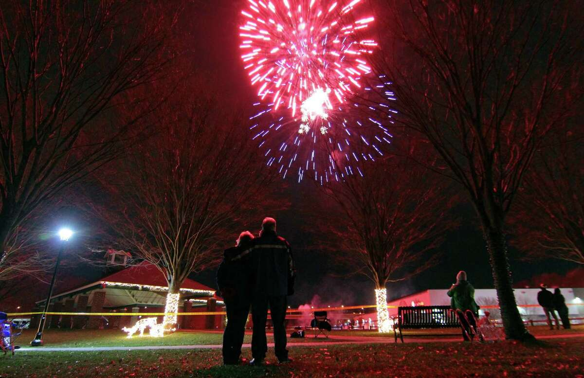 Andrea Wagner of Derby, above, and a couple at right take in the fireworks at Veterans' Riverwalk Park in Shelton New Year's Eve Thursday to ring in the new year.