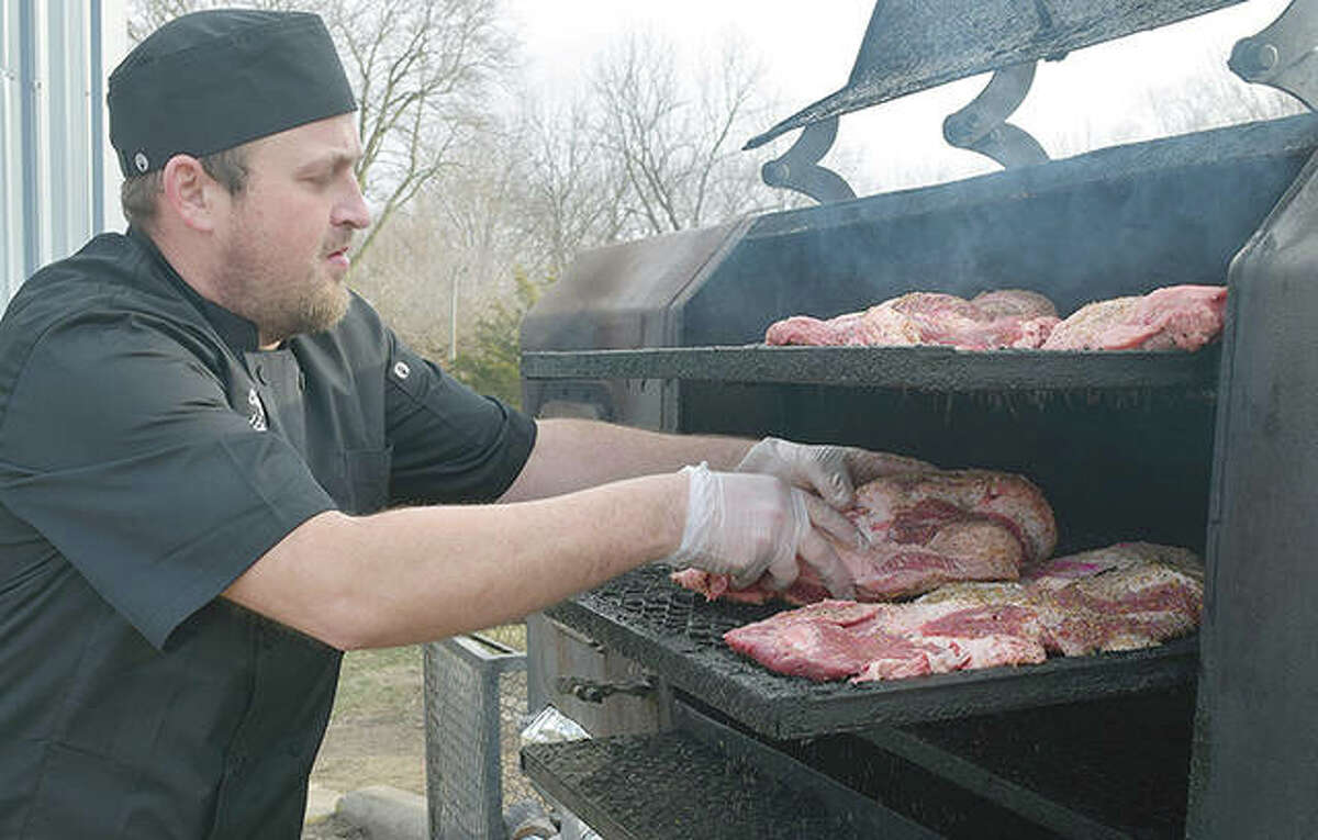 Buddy Fore adds meat to a smoker Thursday at My Buddy's BBQ, 733 E. College Ave.