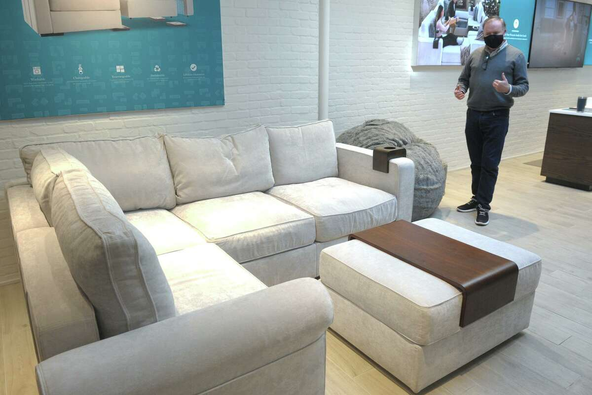 Sales associate Sean Baker shows a sactional in the Lovesac store at 68 Post Road E., in downtown Westport, Conn., on Dec. 23, 2020.
