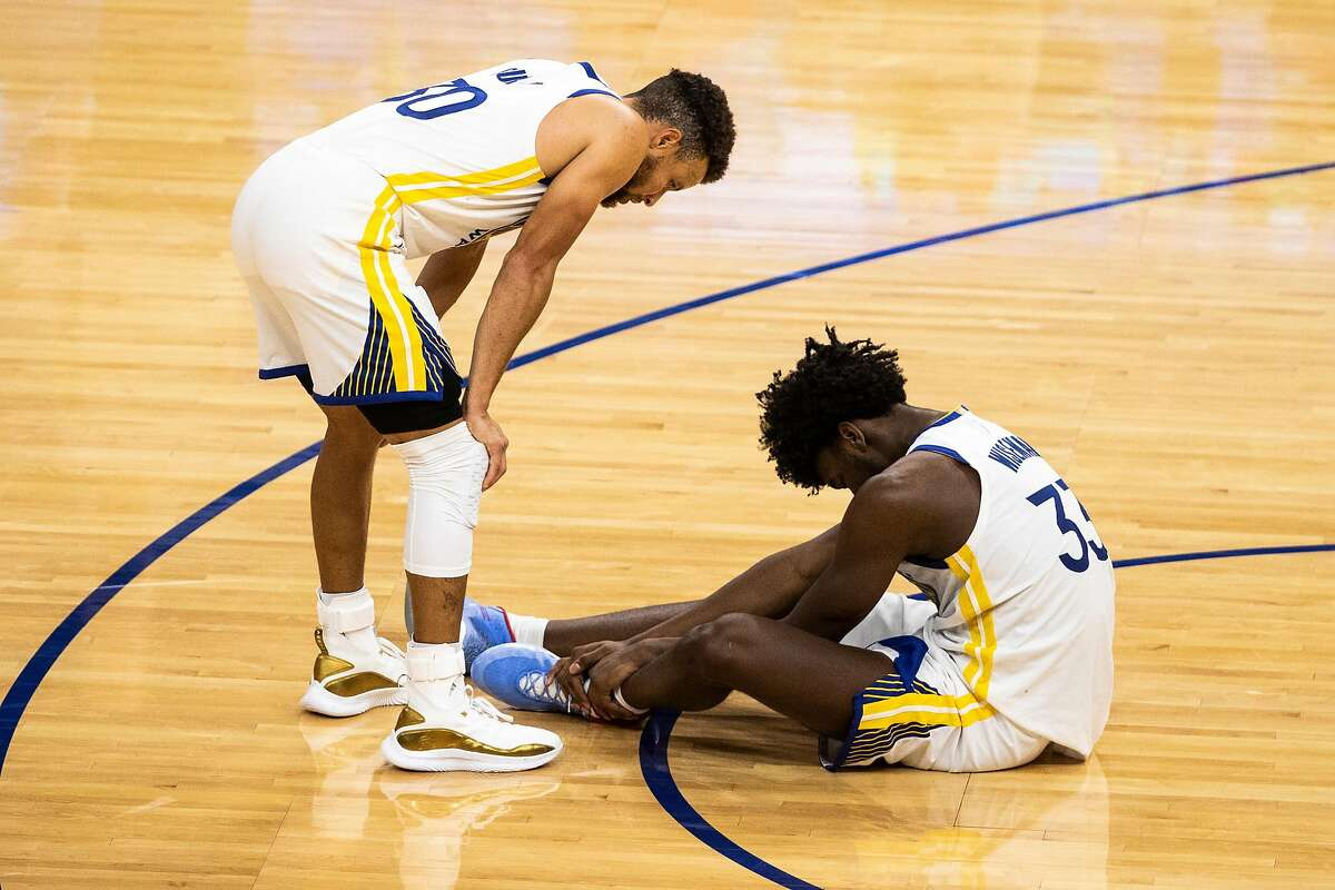 Golden State Warriors guard Stephen Curry (30) checks on teammate James Wiseman (33) after a collision during the fourth quarter of a NBA basketball game against the Portland Trailblazers on Friday, Jan. 1, 2021 in San Francisco, Calif.. The Trailblazers defeated the Warriors 123-98.