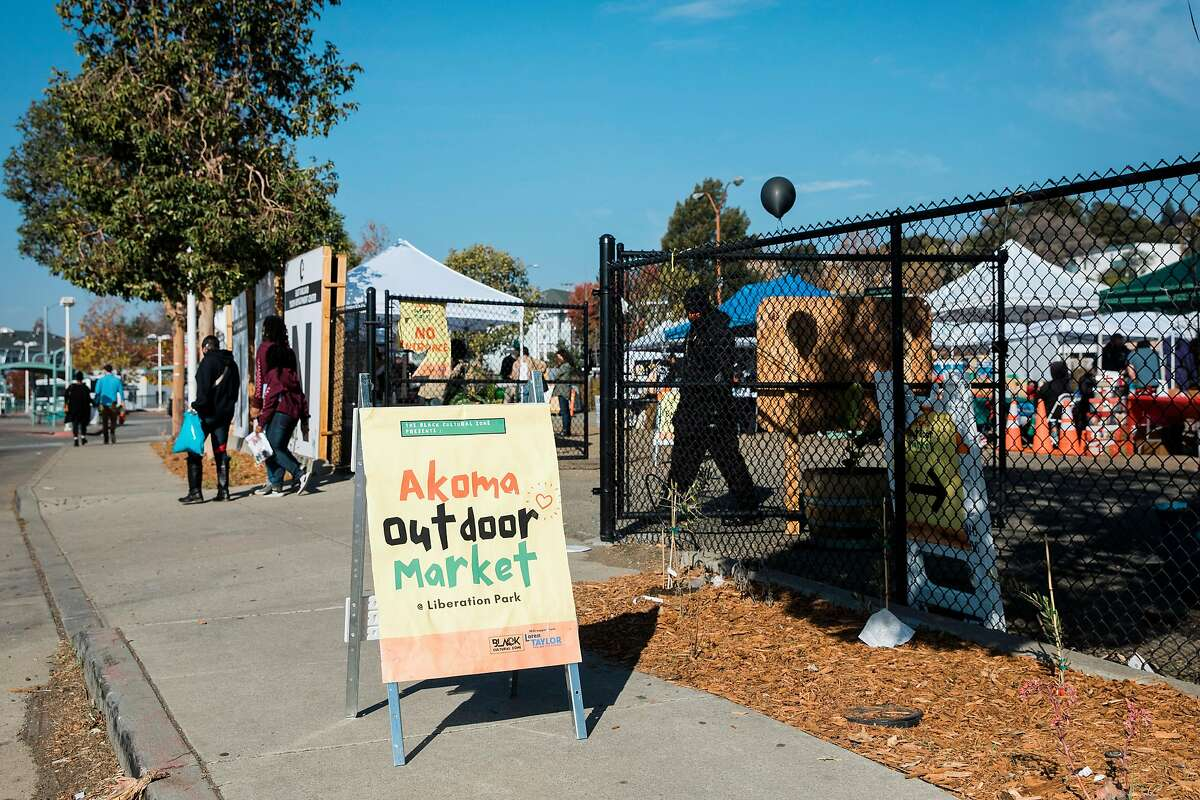 Vendors sell goods at Akoma Outdoor Market in a converted empty space rebranded as Liberation Lot across the street from Eastmont Mall in Oakland.
