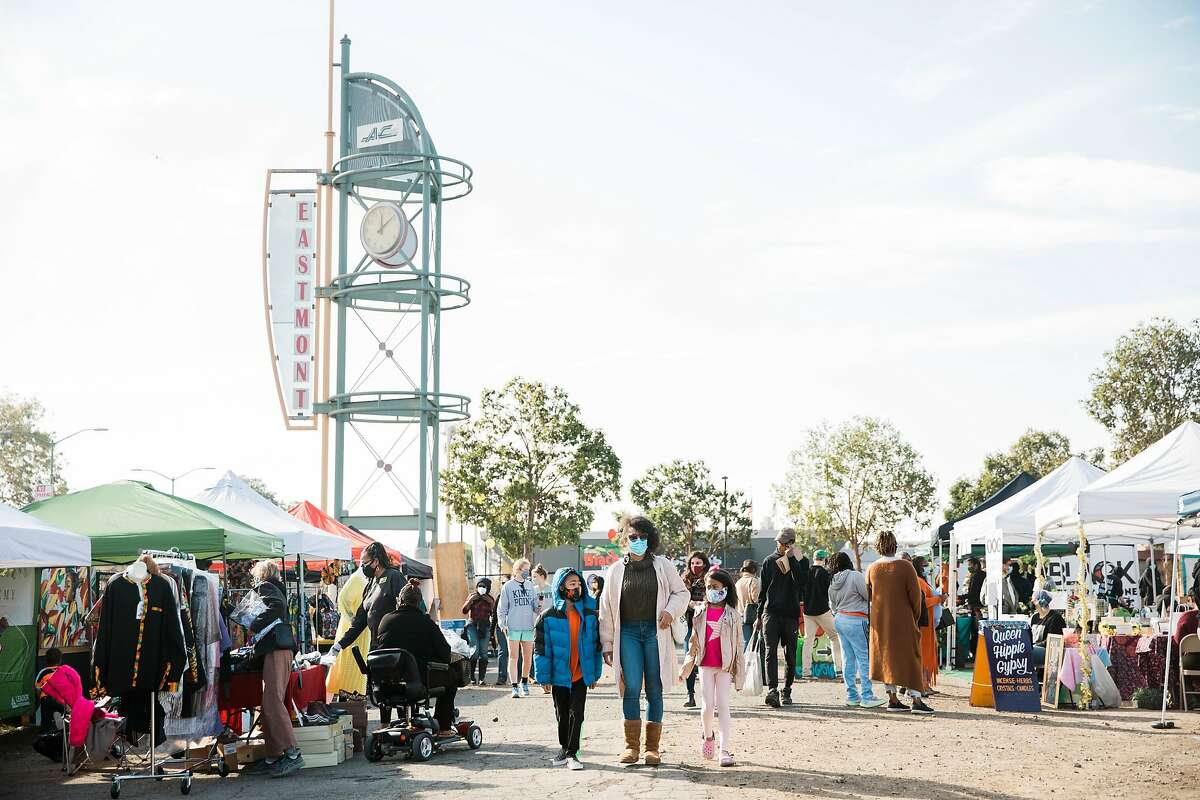 Nina Woodruff-Walker walks with her children, Brooklyn (left) and Brooke, through the Akoma Outdoor Market. The market caters to Black business owners and has helped stimulate economic growth in East Oakland.