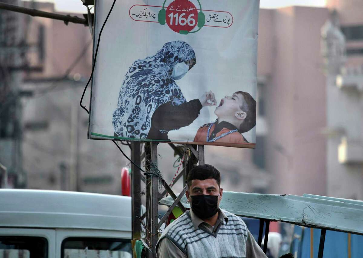 A man wearing a face mask to protect against the coronavirus stands next to a poster promoting a polio campaign at a market in Peshawar, Pakistan, Dec. 14, 2020. The task of vaccinating millions of people in poor and developing countries against COVID-19 faces monumental obstacles, and it's not just a problem of affording and obtaining doses. In parts of Pakistan, it can be outright deadly: More than 100 workers in polio vaccination campaigns have been killed since 2012, as militants spread fears that the inoculations are an anti-Islam plot. (AP Photo/Muhammad Sajjad)