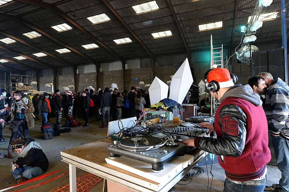 A DJ plays music during a party in a disused hangar in Lieuron about 40km (around 24 miles) on south of Rennes, on January 1, 2021. - A wild party that began on December 31 evening in Lieuron, still gathered on January 1 around 2,500 participants