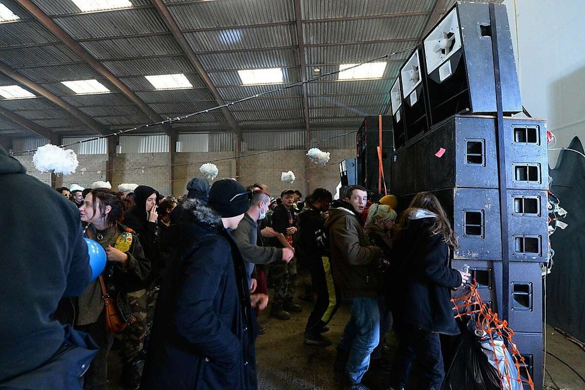 People dance during a party in a disused hangar in Lieuron about 40km (around 24 miles) on south of Rennes, on January 1, 2021. - A wild party that began on December 31 evening in Lieuron, still gathered on January 1 around 2,500 participants