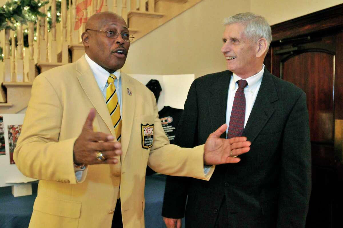 SPORTS-HAMDEN-Pro football hall of famer, Floyd Little (L) talks about the difference that Robert Schreck's (R) encouragement, made in his life. The two men are attending the Gridiron Club Halll of Fame Awards Dinner. Melanie Stengel/Register 12/09/10