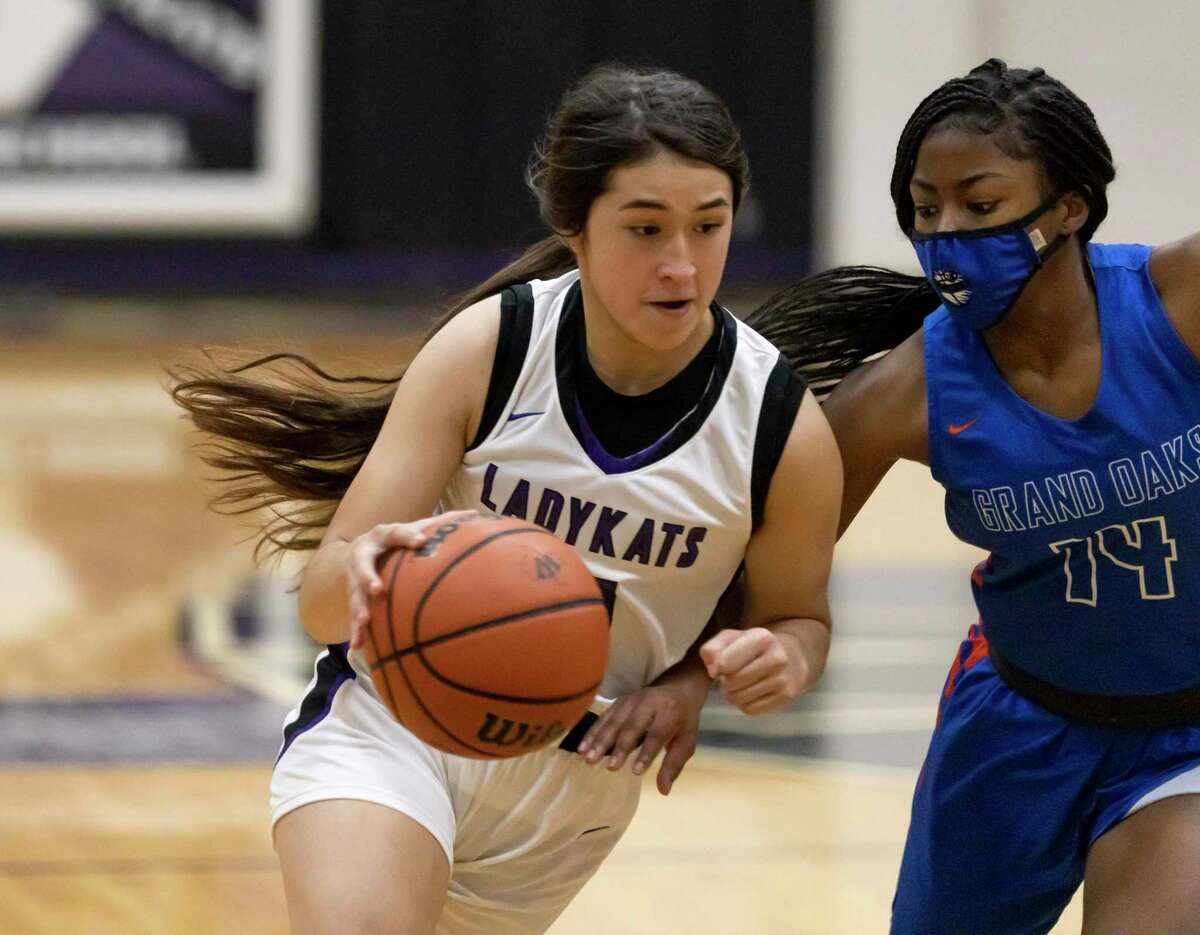 Willis guard Lucy Smith (5) drives the ball while under pressure from Grand Oaks guard Madison McCollister (14) during the first quarter of a District 13-6A girls basketball game at Willis High School, Saturday, Jan. 2, 2020, in Willis.