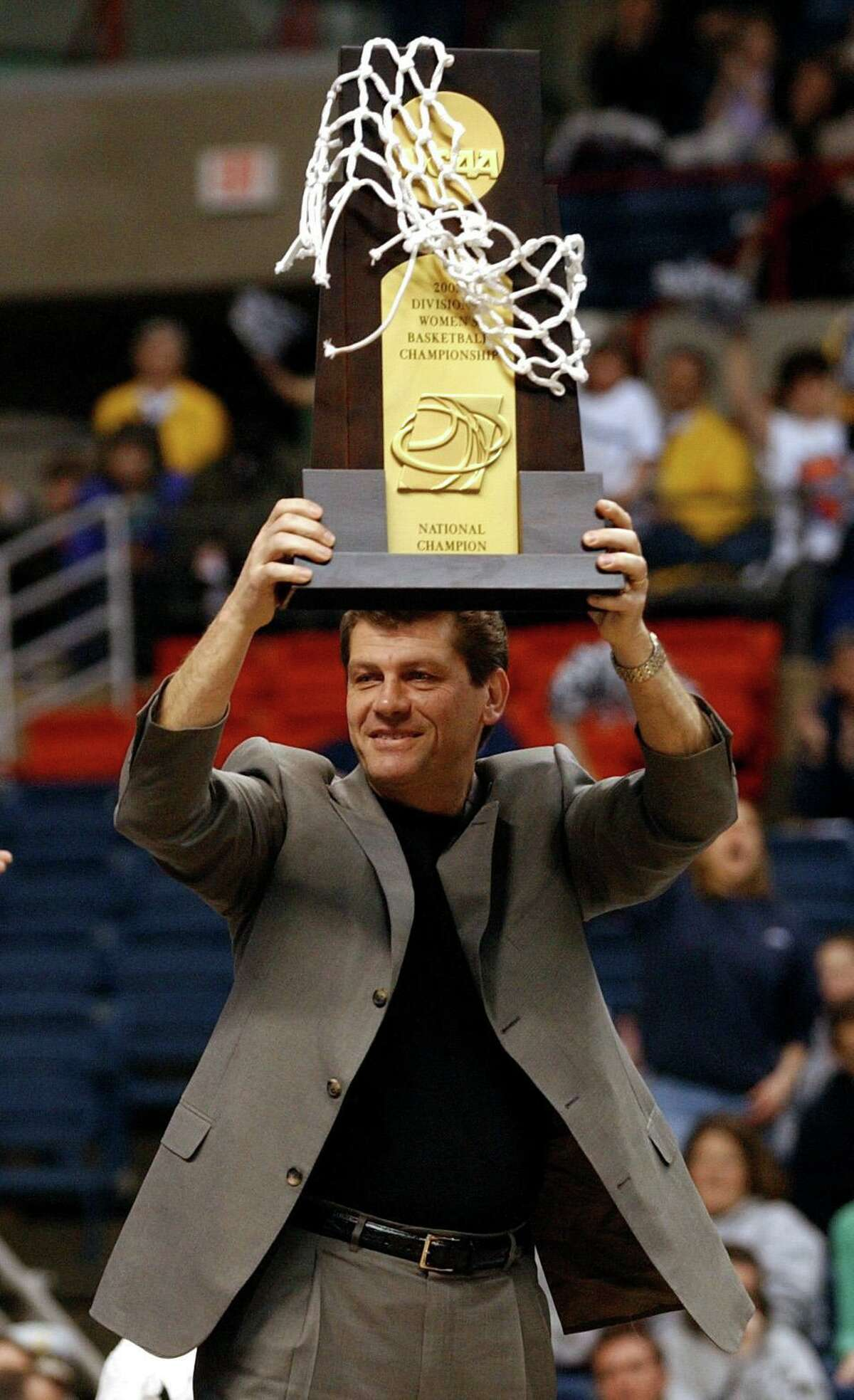 UConn coach Geno Auriemma holds up the NCAA Championship trophy. Aaron in 2002.