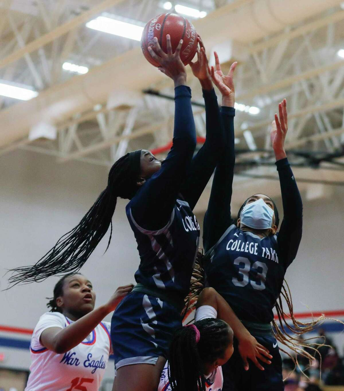College Park forward Ali Diop (10) goes up for a rebound along with forward Bobbi Bazzle (33) during the first quarter of a District 13-6A high school basketball game at Oak Ridge High School, Saturday, Jan. 2, 2020.