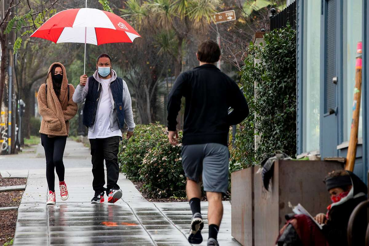 Ferdinand and Amelia Yambao of San Leandro were masks and share an umbrella while walking down Dwight Way near Telegraph Avenue as rain falls over Berkeley, Calif. Saturday, January 2, 2021. Much-needed rain is expected to fall through most of Friday in the Bay Area.