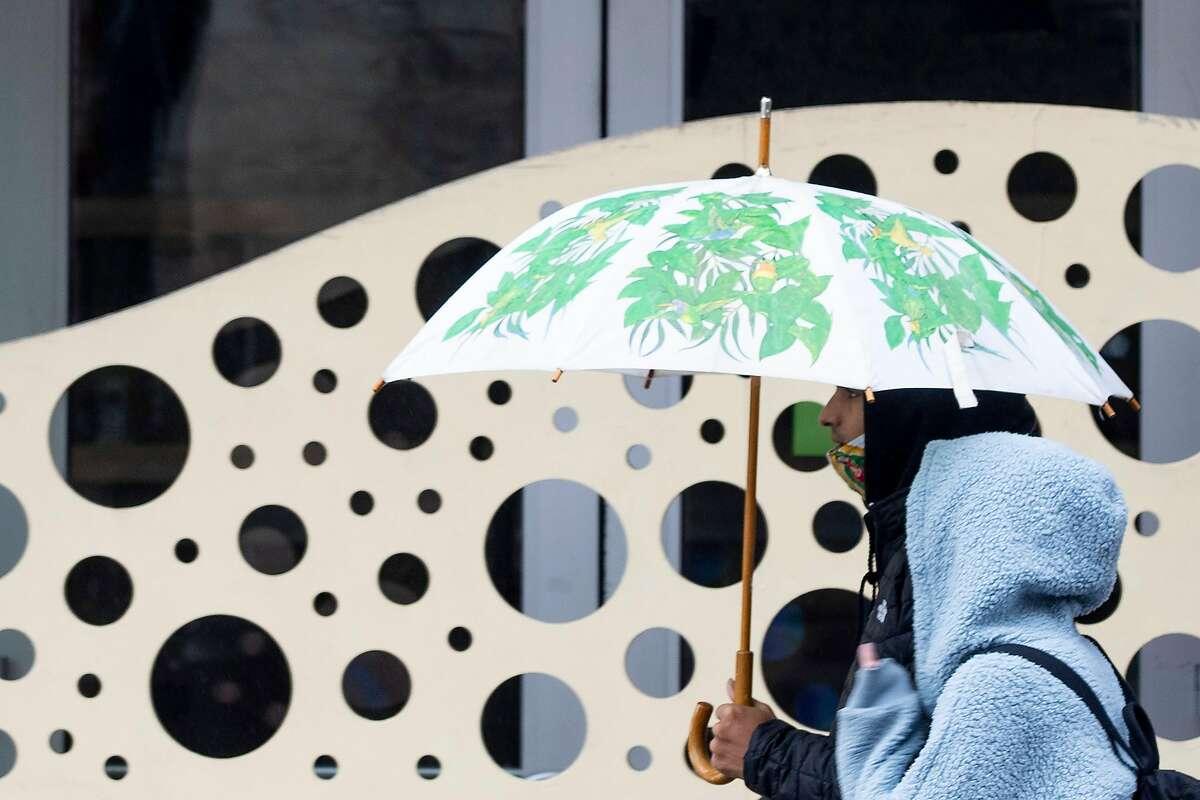 A couple share an umbrella while walking down Telegraph Avenue as rain falls over Berkeley.