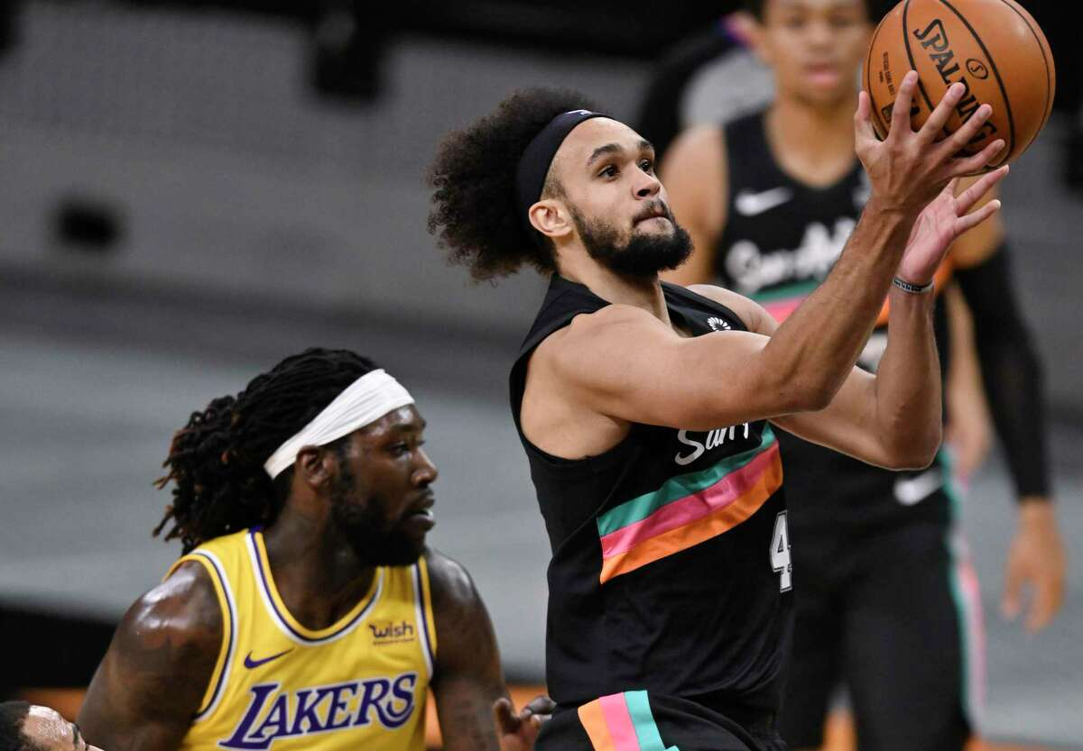 The Spurs' Derrick White (4) shoots against the Los Angeles Lakers' Montrezl Harrell (15) and Talen Horton-Tucker during the first half Friday, Jan. 1, 2021, in San Antonio.