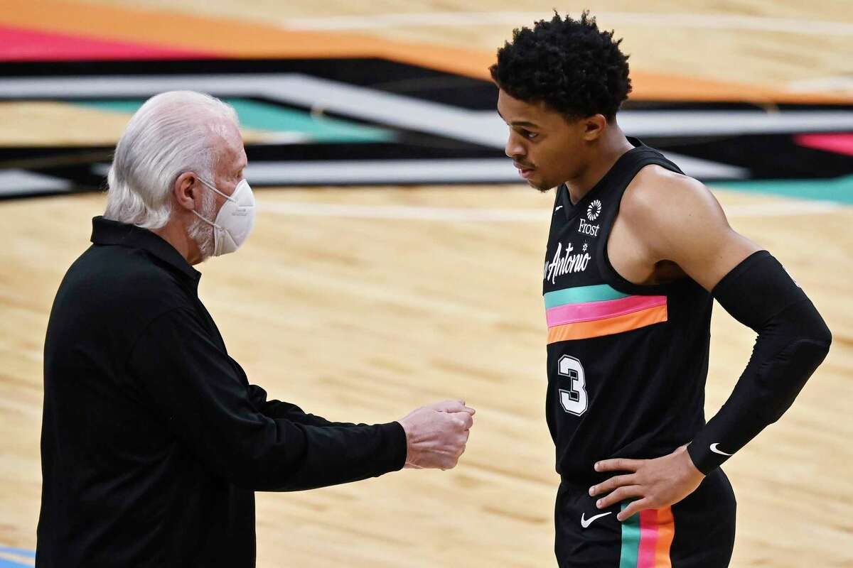 San Antonio Spurs coach Gregg Popovich talks to guard Keldon Johnson during the first half of the team's NBA basketball game against the Los Angeles Lakers, Friday, Jan. 1, 2021, in San Antonio. (AP Photo/Darren Abate)