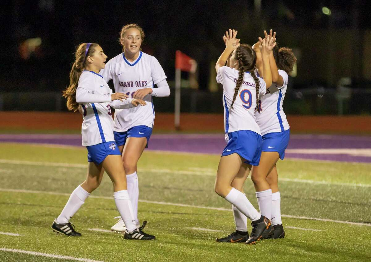 In this file photo, Grand Oaks defender Lauren Moylan (23), Grand Oaks forward Rylee Friedrich (9), Grand Oaks midfielder Reese Rupe (18) and Grand Oaks defender Racquel Mouton (11) cheer as they score during a District 20-5A high school soccer match at Berton A. Yates Stadium, Tuesday, Jan. 21, 2020, in Willis.
