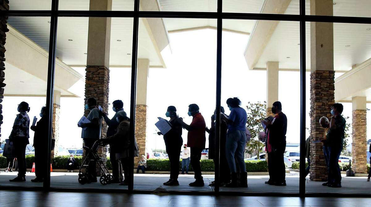 People line up to make appointments for the Houston Health Dept., free COVID vaccine distribution at Bayou City Events Center in Houston on Saturday, Jan. 2, 2021.