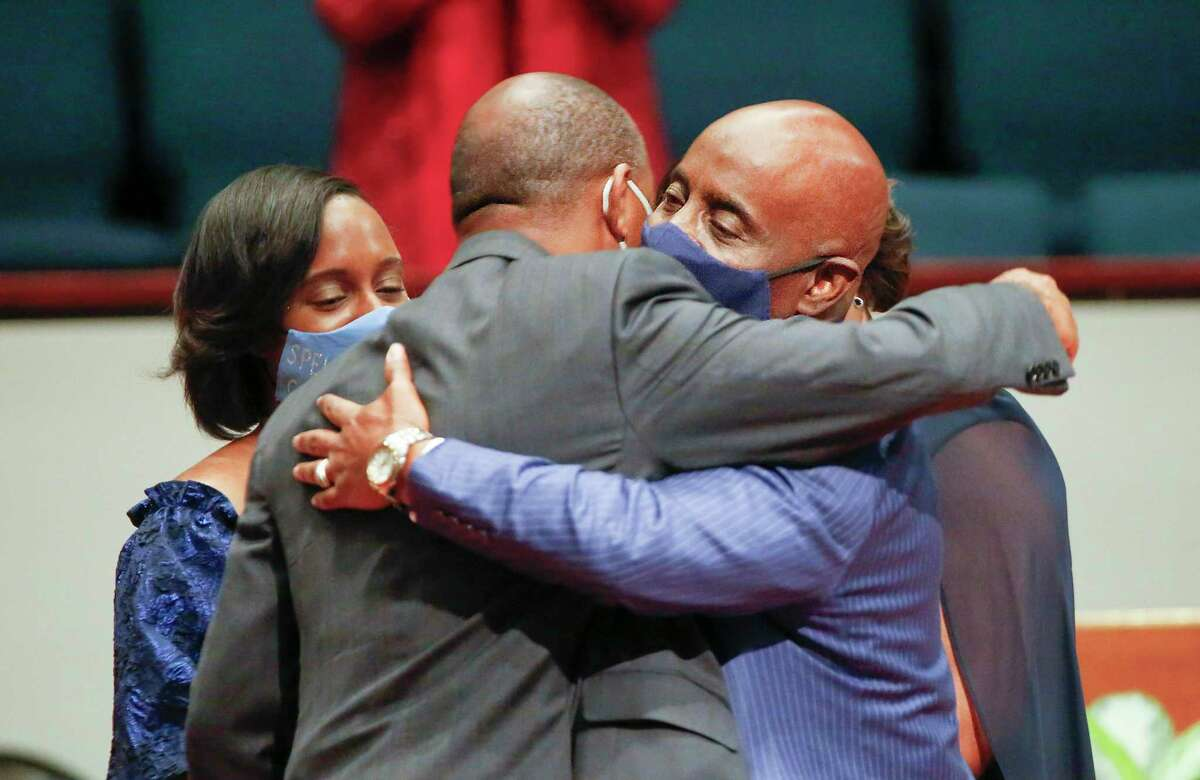 Houston Mayor Sylvester Turner (left) hugs Sheriff Eric Fagan (right) as his daughter Dr. Fallon Fagan looks on after a swearing in ceremony at the Fort Bend Church Saturday, Jan. 2, 2021, in Sugar Land. Sheriff Fagan became the first African American to be Fort Bend County Sheriff in over 150 years.