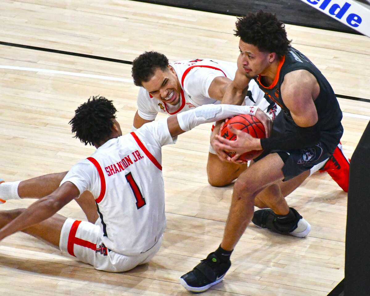 Texas Tech's Marcus Santos-Silva (middle) and Terrence Shannon, Jr. fight with Oklahoma State's Cade Cunningham for the ball during the Red Raiders' 82-77 loss to the Cowboys on Saturday in the United Supermarkets Arena at Lubbock.